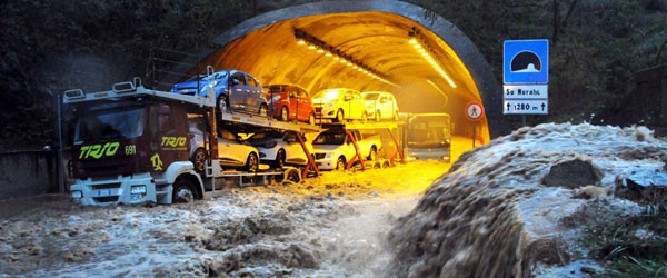"In this photo taken on Monday, Nov. 18, 2013 a truck and a bus are stranded by flood waters in a tunnel near Olbia, Italy. The Mediterranean island of Sardinia, prized by the jet-set for its white sand beaches and crystal-clear seas, was a flood-ravaged mud bath Tuesday after a freak torrential rainstorm killed at least 17 people, downed bridges and swept away cars. Olbia Mayor Gianni Giovannelli said the city had been destroyed by the ""apocalyptic"" storm, with bridges felled and water levels reaching 3 meters (10 feet) in some places. He described the ferocity of the storm's rains as a ""water bomb."" (AP Photo/Massimo Locci)"